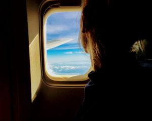 Woman looking out of plane window